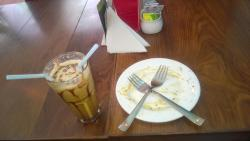 Yummy cold coffee and empty plate of cheese pasta