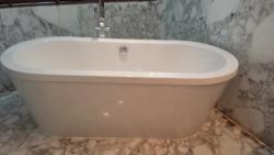 Free standing tub with water damage on marble