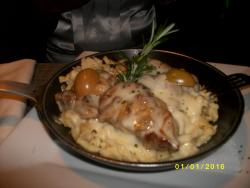 Pork fillet on home made pasta with mushroom and cheese on top .