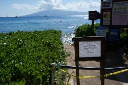 Sign saying access to the beach is closed (no beach in front) due to erosion.