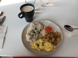 Biscuits with sausage gravy, scrambled eggs, café au lait