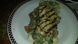 Chicken and chicken with sauce and veggies on a biscuit