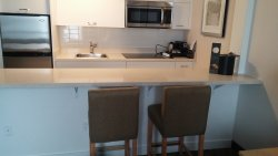 Kitchenette with full fridge, microwave, coffee machine, dinnerware (dishes, cutlery, cups).