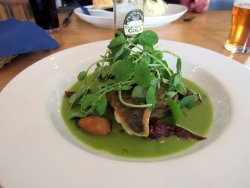 Pan Seared Sea Bass on a courgette & potato rosti with pea sauce, pea shoots and smoked mussles.