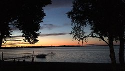 Sunset on Lake Bemidji with volleyball net and beach in the foreground.