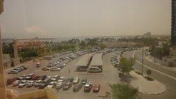 vue de la chambre sur le parking avec la mer au fond
