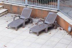 vuil rond zwembad toaal niet onderhouden van zwembad en ruimte waar ligstoelen staan ..