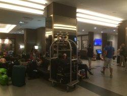 Réception de l'hôtel où s'entassent bagages et clients assis par terre