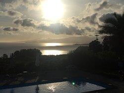 uitzicht vanaf balkon op zwembad, zee en zonsopgang