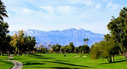 Golf course fairway with view of snow-capped mountains.