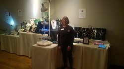 The Artist who created the jewelry on the table behind her. It was very nice looking.