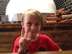 My 7 year old awaiting his birthday pizza from the wood fired oven behind him!
