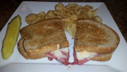 Reuben with kettle chips and pickle.