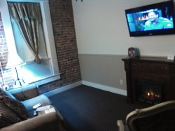 Very roomy sitting area. Fireplace, couch and chair.