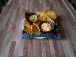 Una entradita de nachos con guacamole y queso cheddar