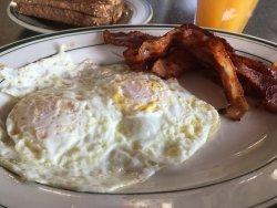 Eggs (over medium), bacon, and multigrain toast