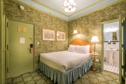 Jr Suite guest room, two rooms one with a queen bed the other with a day bed separated by arch w