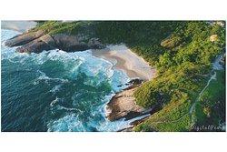 Imagem aérea da praia e o acesso pelo canto direito da foto.