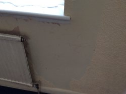 Wallpaper peeled off wall radiator blak with dirt and grease