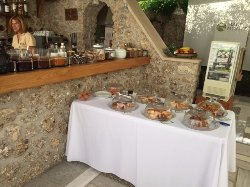 Breakfast table set with strapatsada, homemade pies and cakes. Homemade marmalades, honey, cerea