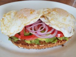 Avocado Toast - Sunflower seed bread, tomatoes and red onion topped with 2 sunny side up eggs DE