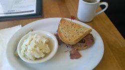 Half sandwich (NY turkey pastrami) with potato salad, pickle, and organic coffee.
