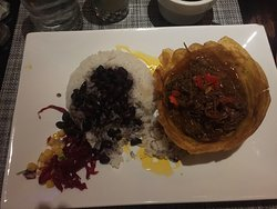 Ropa Vieja in a plantain shell with Black Beans and RIce.