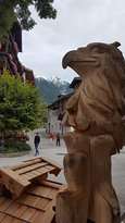 carved in wood vulture with a beatiful mountains panorama (279778818)