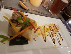 5 spiced duck spring roll, sweet chilli, hoisin, mango set upon banana leaf.