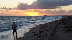 Рассвет на пляже отеля (отдыхающие ищут на берегу раковины или бегают трусцой)