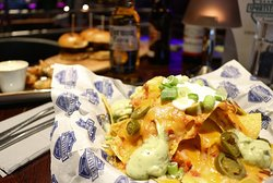 Mini Nacho Stack Topped with Cheddar Cheese, Salsa, Sour Cream, Jalapenos & Guacamole (v)