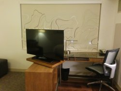 TV on swivel stand with desk in view and office chair