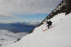 Skiing down Mount Rombakstötta with the city of Narvik below