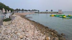 Digue en pierre suivie d'une plage et d'espaces verts