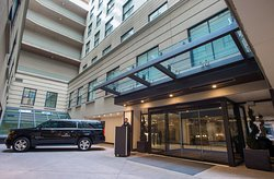 The Front Entrance of the Magnolia Hotel with the Hotel's Courtesy Vehicle (1 mile radius)
