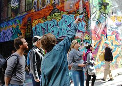 our tour guide pointing point different style of street art to the group