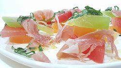 Compressed melon with prosciutto, basil, lemon, and extra virgin olive oil.