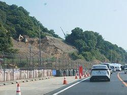 ビーチの駐車場を道路に使用しています。左上が高速道路の修復工事です。
