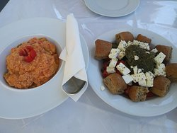 Thirasia salad and a hot dish with potatoes, zucchini and tomato and cheese.