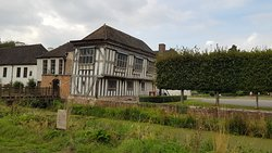 The old timber framed building seen from the other side of the moat.