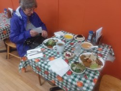 Tables with hot and cold items, soups, tea, filtered water, and desserts