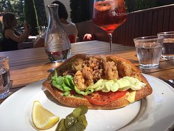 Calamari panino on housemade baguette, with an Aperol spritz on the patio