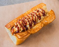 COWBOY – smoked bacon wrapped dog, cheddar cheese sauce, bbq sauce, crispy onions
