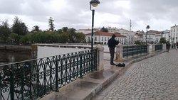 Guy providing musical entrainment on the bridge