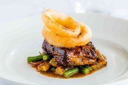 Braised beef short rib with gnocchi, green beans, and onion rings.