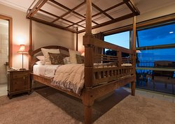 Waitangi Room with 4 poster bed, balcony with gorgeous sea views and a bathroom complete with spa bath looking out to the sea