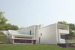 """""""归隐""""别墅由中国建筑师周恺设计而成。该建筑依托地形自然变化设计,体现了建筑师""""与自然融为一体""""的设计理念。极简的设计手法突出了简单的线条,以及可与相邻庭院和景观重新组合的空间结构,给人开阔宽敞的感觉。"""
