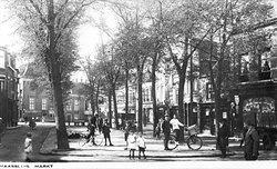 Stemmige ansichtkaart van de Markt op een mooie dag gezien in de richting van de Nieuwstraat. Achteraan op het middenpad is de visbank zichtbaar en tussen de bomen door zien we de bus naar Delft gereed staan voor vertrek. (bron: HVM)