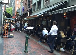 The Grill Steak and Seafood sign is visible in this busy sidewalk alley.
