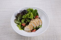 Grilled chicken salad with tomato and organic vegetables in Chef's homemade salad dressing